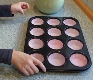 Alina hat die Muffinform mit Papierförmchen ausgelegt.